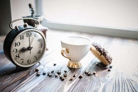 vintage alarm clock showing 9am on the table next to a cup of coffee and a donut. Breakfast. Time management concept.