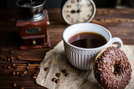 glass of coffee on table with clock in morning. vintage alarm clock showing 9am on the table next to a cup of coffee and a donut. Breakfast. Time management concept