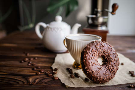 Chocolate donut for morning breakfast. White vintage Coffee Cup With Beans On Rustic Table