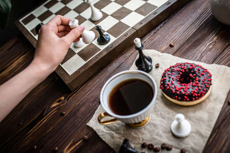 hand holds a white vintage cup of coffee. Chess board and scattered chess on wooden table. Chocolate donut for morning breakfast. board game Concept 免版税图像