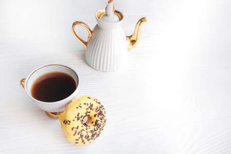White vintage teapot and cup of coffee on white wooden background. Sweet breakfast 免版税图像