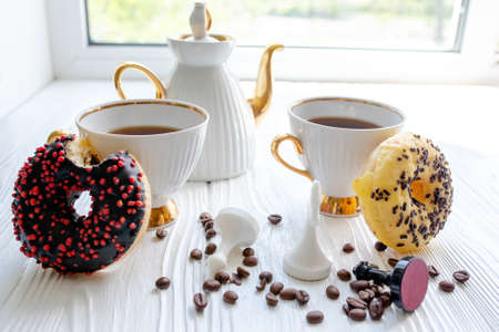 Sweet breakfast lovers. A donut on a white table. Two vintage cups of coffee and a teapot in the background of the window.