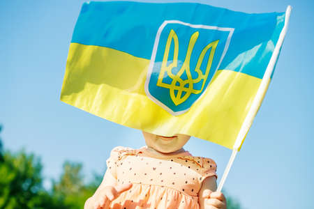 girl holding flag of Ukraine. Blue yellow flag of Ukraine with coat of arms in hands of child on Independence Day and Flag Day