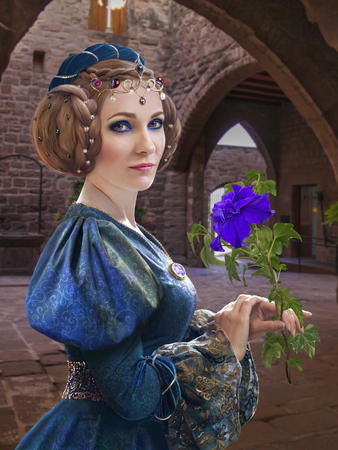 medieval dress: Medieval portrait of a young woman with a flower in her hand Stock Photo