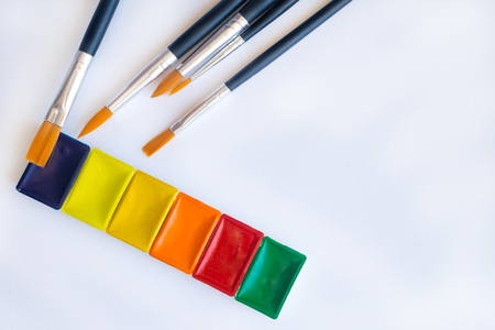 Photo of brushes for water color painting close up and set of watercolor paints in cuvettes