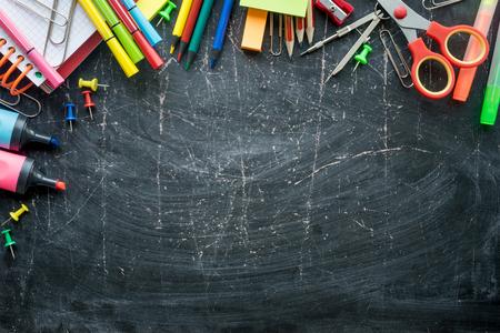 Granica przyborów szkolnych na tle tablicy. Wolna przestrzeń