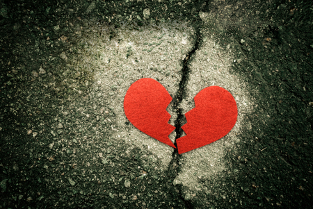 Broken red heart on cracked asphalt. divorce concept. Standard-Bild