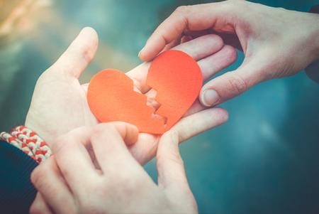 Manos masculinas y femeninas que reparan un corazón roto. Concepto de divorcio. Concepto de amor