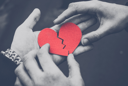Zwart-wit foto van mannelijke en vrouwelijke handen die een gebroken hart herstellen. Echtscheiding begrip. Liefdesconcept. Afgezwakt. Zwart en wit Stockfoto