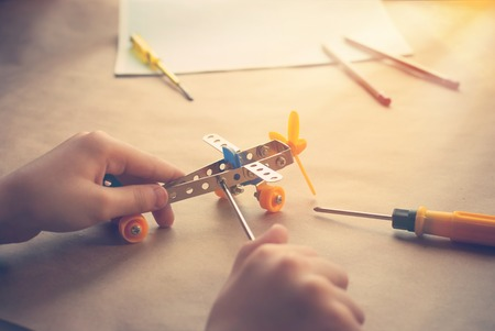 Children hands with Toy iron plane. Metal constructor of aircraft with screwdrivers on the table.