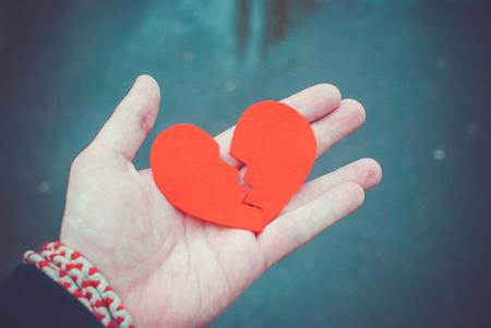 Concepto de divorcio - corazón rojo roto en manos masculinas.