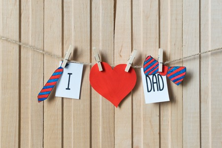 Fathers day concept. Message with paper hearts, tie and bow-tie hanging with pins over light wooden board. Imagens - 121936470