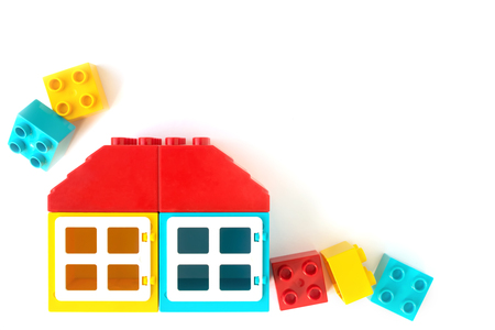House made of colorful plastic constructor bricks on white background.