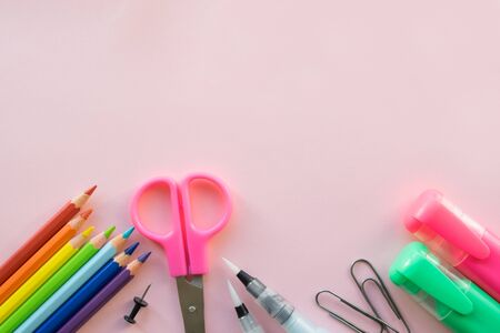 School and Office drawing supplies on pink background. Free space for text. Back to school. Top view border of colour pencils, markers, scissors and brushes