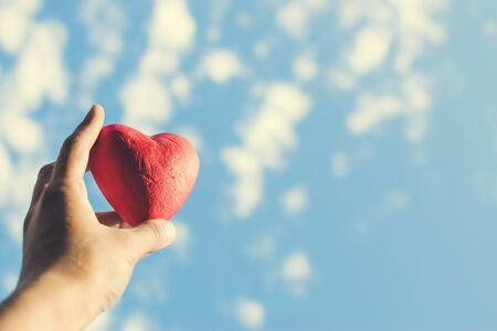 Hand holding the red decorative heart against the blue sky. Day of donor. Love concept. Toned photo