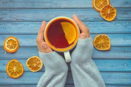 Hot warming tea with orange in female woman hand on blue wooden table 版權商用圖片