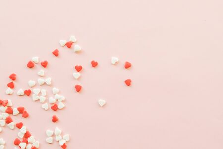 Valentines Day background with red and white little hearts on pink backdrop. Valentines day concept. Copy space.