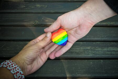 Decorative Heart with rainbow stripes in male hands. LGBT pride flag, symbol of lesbian, gay, bisexual, transgender for social movements. Homosexual love, Human rights concept. Copy space. Archivio Fotografico