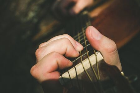 Fingers forming a chord on a guitar fingerboard. Male hand playing on guitar. Selective focus