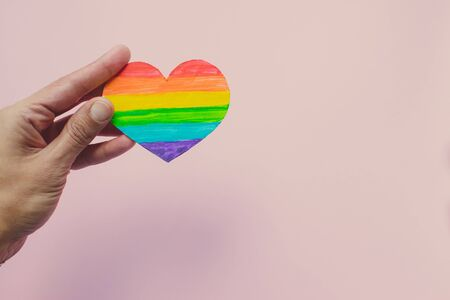 Female hand holding decorative Heart with rainbow stripes on pink background. LGBT pride flag, symbol of lesbian, gay, bisexual, transgender. Homosexual love, Human rights concept. Copy space. 版權商用圖片