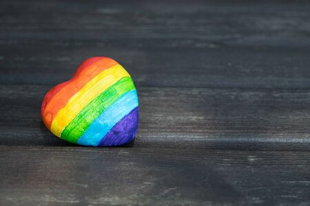 Decorative Heart with rainbow stripes on dark wooden background. LGBT pride flag, symbol of lesbian, gay, bisexual, transgender for social movements. Homosexual love, Human rights concept. Copy space.