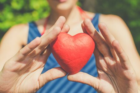 Relationship and love concept - womans hands holding red heart