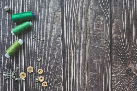 Sewing accessories on dark wooden background. Green sewing threads, needle, buttons and pins. top view, flatlay