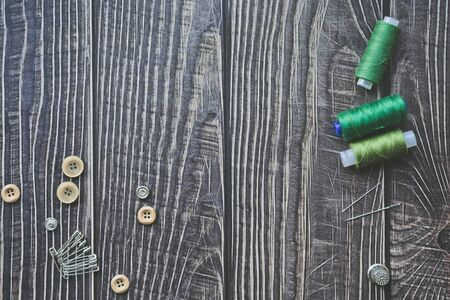 Sewing accessories on dark wooden background. Green sewing threads, needles, buttons and pins. top view, flatlay