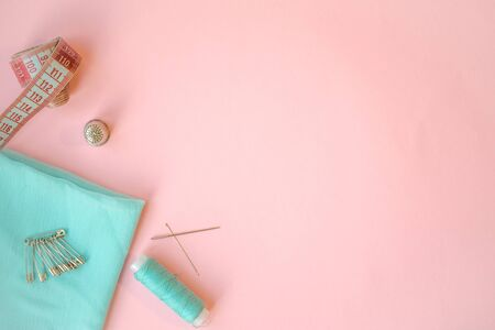 Sewing accessories, turquoise fabric on pink background. Fabric, pins, threads and needles. Stock Photo