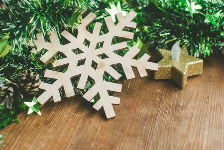 Christmas background with decorative composition of green tinsel, wooden snowflake, candle and pine cone on wooden board.