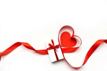 Top view of ribbon shaped as heart and gift box isolated on white background. Valentines day concept.