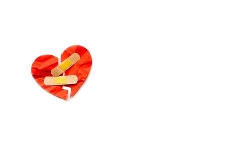 Broken red heart symbol with medical patch on white background, love concept. healing