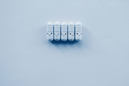 Row of Funny classic blue toned capsule on blue background. Copyspace. Top view.