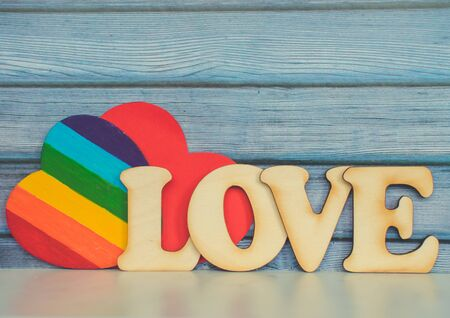 Valentines Day card background, Rainbow cute heart like a LGBT pride rainbow flag with red paper heart and decorative wooden word. Valentine Day romantic. Love human rights and freedom concept. 版權商用圖片
