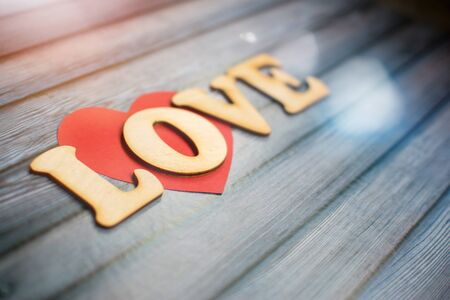 Valentines Day card background, red cute heart made of paper with decorative wooden word on blue background. Valentine Day. Love concept. Selective focus. Copyspace