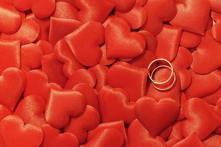 Valentines day many red silk hearts background with two gold rings, love concept 版權商用圖片