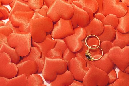 Two golden wedding rings on red satin hearts background