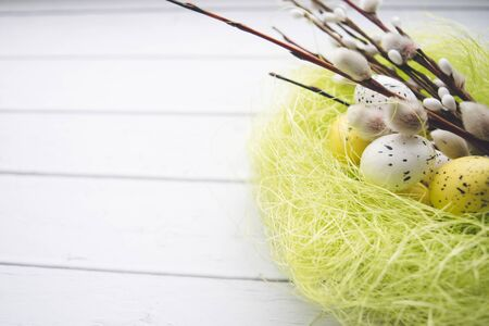Easter decorations. Willow twigs and decorative Eggs in nests on wooden background 版權商用圖片