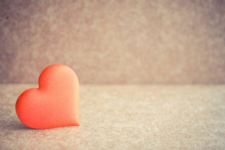 Red heart on the wooden desk background. Copyspace