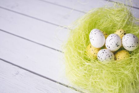 Easter decorations. Eggs in nests on white wooden background 版權商用圖片