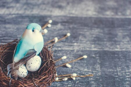 Easter basket with easter eggs and decorative blue bird on wooden background. Selective focus. 版權商用圖片