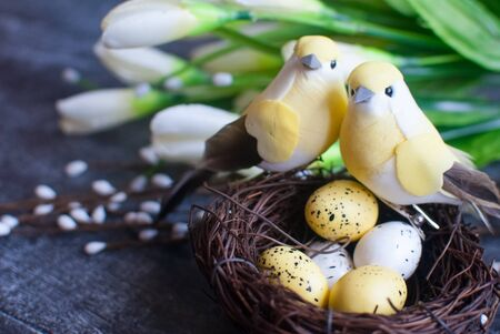Easter background. Nest with easter eggs and decorative yellow bird on wooden background. 版權商用圖片