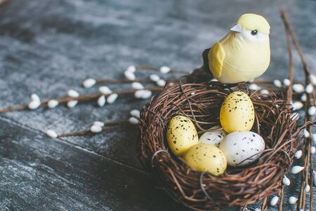 Easter background. Nest with easter eggs and decorative yellow bird on wooden background. Selective focus. Copyspace
