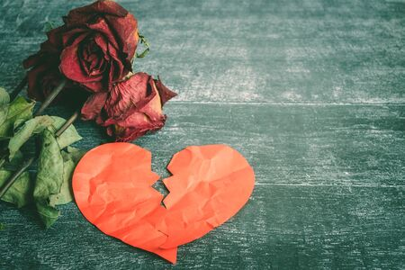 Divorce concept - red broken heart with old rose on wooden background.
