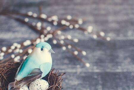 Easter background. Nest with easter eggs and decorative blue bird on wooden background. Selective focus.