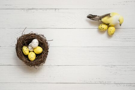 Easter background. Nest with easter eggs and decorative yellow bird on white wooden background. Copyspace. Top view