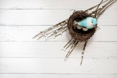 Easter background. Nest with easter eggs and decorative blue bird on white wooden background. Copyspace. Top view