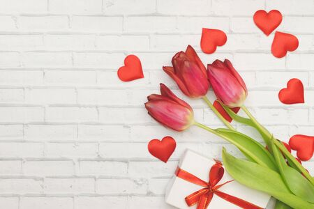 Red Flowers tulips, hearts and gift box with red bow on a white background of wall of brick, spring and holidays, Women's Day. Valentines day, birthday Copyspace