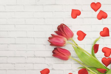 Red Flowers tulips and hearts on a white background of wall of brick, spring and holidays, Women's Day. Copyspace 版權商用圖片
