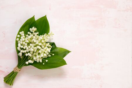 Bouquet of flowers lily of the valley on pink table, top view, space for text, flat lay. 版權商用圖片